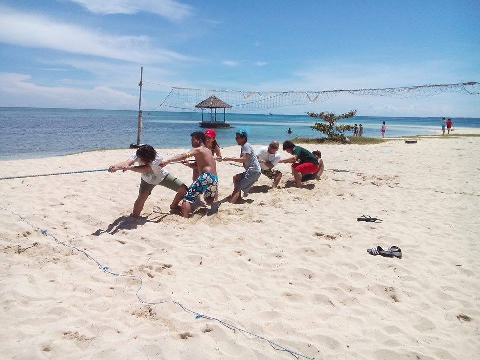 playing tug of war on the beach's vast, white sands