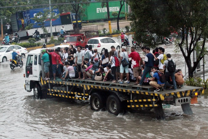 FLOODED NRA/JULY 27, 2015: A cargo truck offers a ride to the stranded people at Kaohsiung street North Reclamation Area Cebu City cuase by a heavy rain.(CDN PHOTO/JUNJIE MENDOZA)