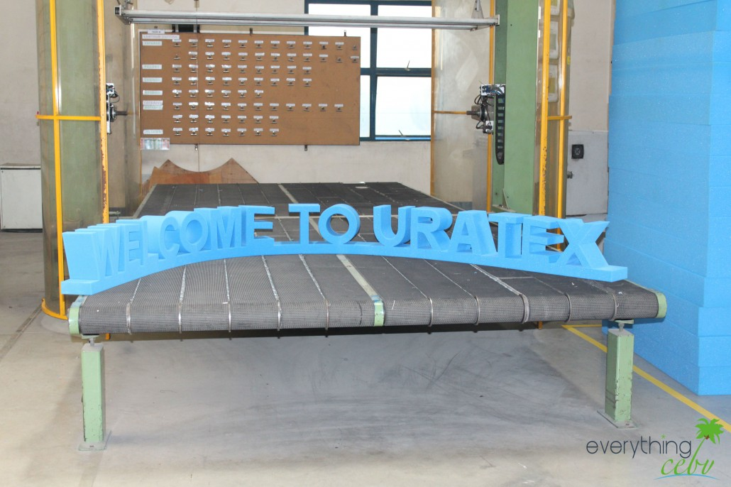 "the ""Welcome to Uratex"" sign made of foam in the plant's cutting area"